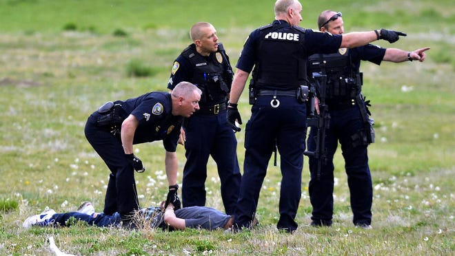 Great Falls police apprehend William Sutherland in an empty field across from the Hilton Garden Inn on April 22, 2015, after responding to shots fired on Park Garden Road.