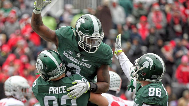 MSU's LJ Scott (3) celebrates with Josiah Price (82) after scoring a touchdown against Ohio State. Scott rushed for 160 yards on the day.