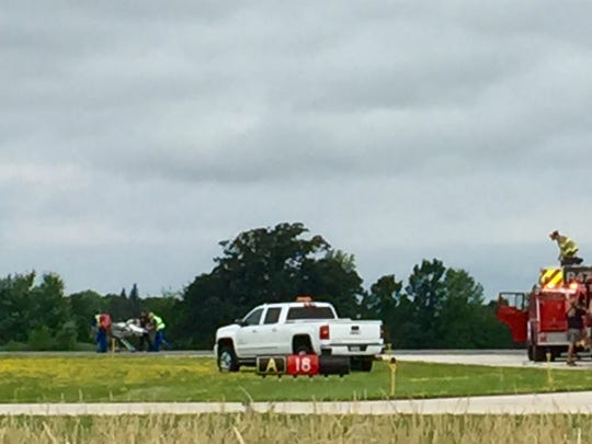 An occupant of the crashed plane is taken to a helicopter to be flown to a hospital.