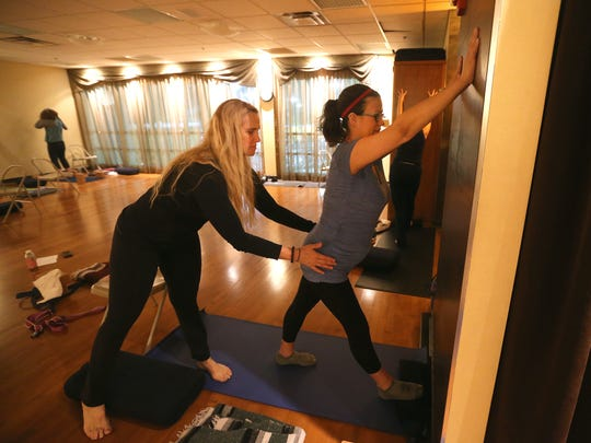 Yoga instructor Leslee Schenk Trzcinski works with reporter Victoria Freile during a gentle yoga class at Midtown Athletic Club.