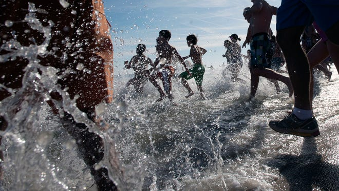 Crowds of people rush into the ocean as the 19th annual Leo Brady Exercise like the Eskimos Plunge ensues Thursday, Jan. 1 in Bethany Beach.
