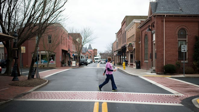 A woman crosses Main St. Wednesday, March 11 in downtown Berlin.