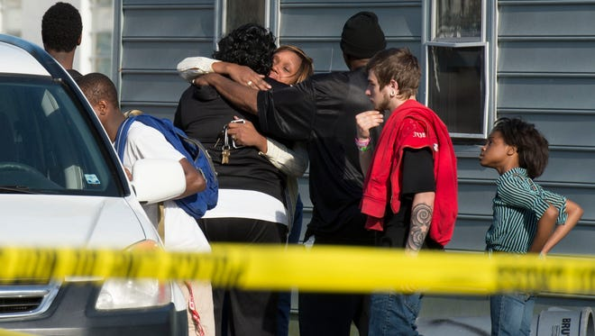Onlookers react as bodies are removed from an Antioch Avenue residence where police say seven children and their father were found dead Monday afternoon in Princess Anne.