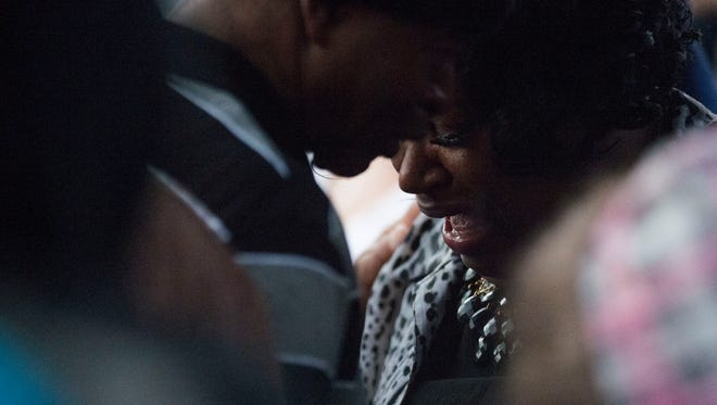 Lloyd Edwards consoles his wife Bonnie Edwards, as she mourns the loss of her son Rodney Todd and her seven grandchildren in a prayer vigil Friday night, April 10 in Princess Anne.