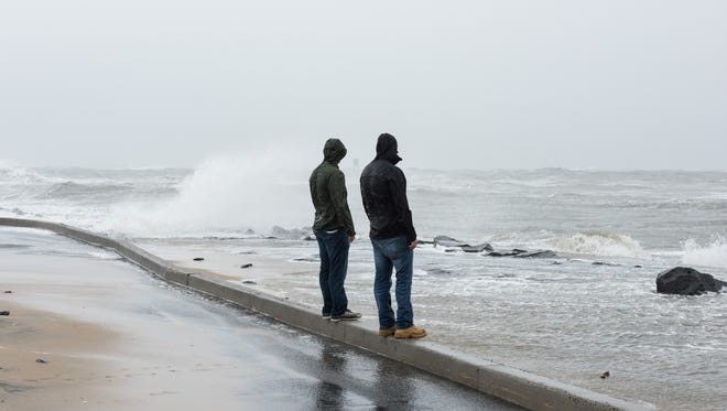 Two men watch the waves crash into the inlet parking lot.