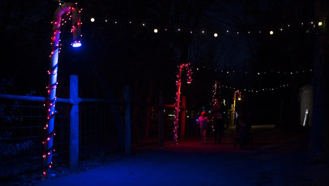 Families walk down a decorated pathway as the Cohanzick Zoo hosts its Festival of Lights Thursday evening, Dec. 3 in Bridgeton.