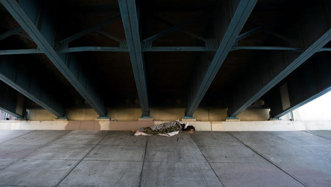 A homeless man sleeps under Flanders Ave at the intersection of U.S. Hwy 30 in Camden.