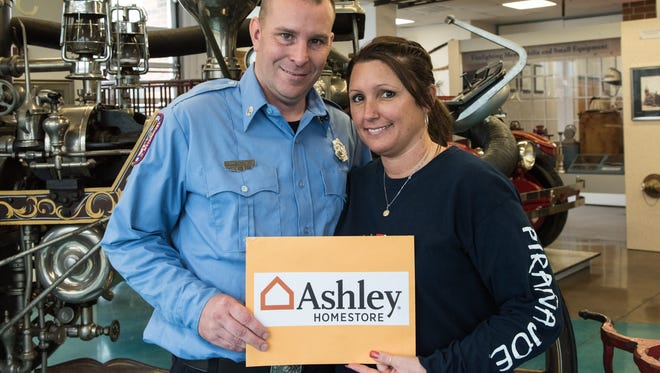 Donnie and Kara Phippin, of Hebron, pose for a photo at the Salisbury Fire Department on Cypress Street on Thursday, Feb. 25, 2016.  After a Jan. 28 house fire destroyed their home, Ashley Homestore awarded them a large check to replace some of their furniture.