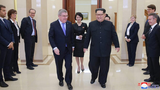 In this photo provided by the North Korean government on Saturday, March 31, 2018, North Korean leader Kim Jong Un, center right, walks with International Olympic Committee President Thomas Bach, center left, during a meeting in Pyongyang, North Korea.