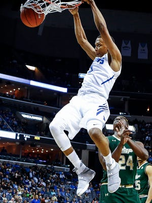 University of Memphis forward Jimario Rivers (left) completes a dunk in front of  University of South Florida defender Malik Fitts  (right) during first-half action at the FedExForum.