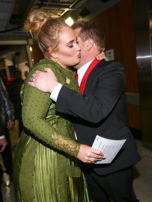 Grammy winner Adele, left, gives a hug and kiss to friend and first-time host James Corden at Sunday's ceremony.