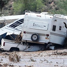 An RV is pilled on top a pickup truck and a horse trailer as flood water runs high in New River on Tuesday, Aug. 19, 2014.