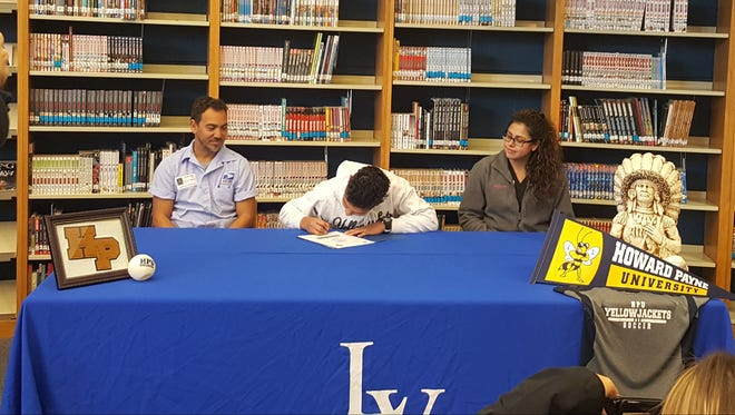 Lake View High School's Zibby Munoz signs a letter of intent to play soccer for Howard Payne University while father Piero Munoz and mother Blanca Munoz look on at the Lake View library Monday, Dec. 11, 2017.