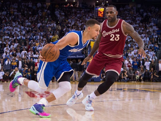 Stephen Curry dribbles against LeBron James in the
