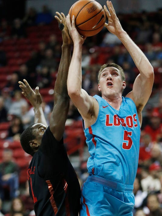New Mexico's Joe Furstinger shoots over UNLV's Cheickna Dembele during the first half of an NCAA college basketball game Wednesday, Jan. 17, 2018, in Las Vegas. (AP Photo/John Locher)