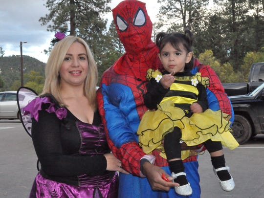 A family dressed in the  Halloween spirit and lined