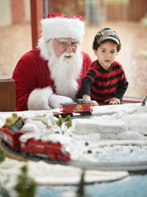 Santa Claus takes a few moments to play with Gatlin Timberlake, 4, of Carriere at Bass Pro Shops in Pearl.