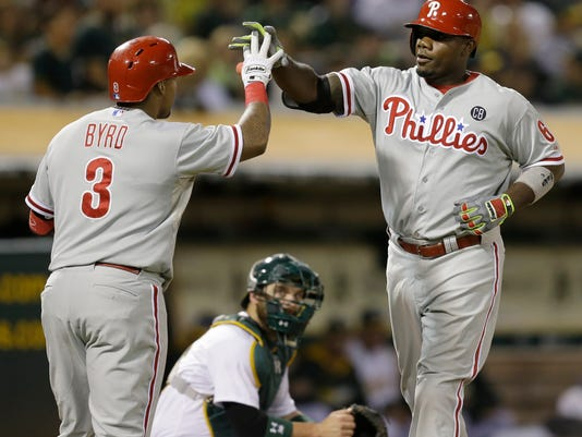 Philadelphia Phillies' Ryan Howard, right, is congratulated by Marlon Byrd (3) after hitting a home run off Oakland Athletics' Jon Lester in the fourth inning of a baseball game Friday, Sept. 19, 2014, in Oakland, Calif. (AP Photo/Ben Margot)