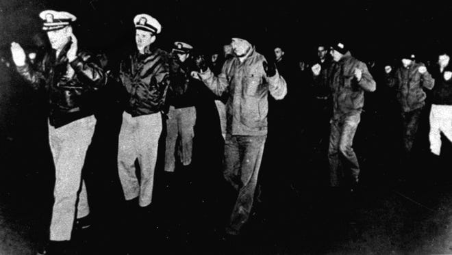 Crew members of the USS Pueblo are led into captivity after the vessel was seized by North Korean patrol boats in the Sea of Japan in January 1968.