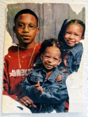 This picture of Ajani Miller, left, his daughter Q'ajaniyah, right, and Q'ajaniyah's cousin was taken two weeks before Ajani Miller was killed in 1999. The picture hangs on the refrigerator in Q'ajaniyah Miller's home, and is the only one she has of her father.