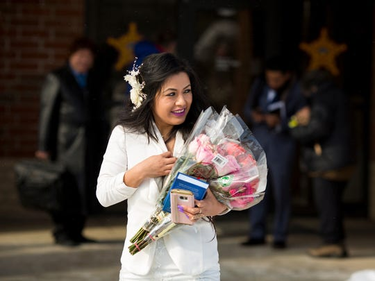 Sandra Mendoza leaves the Morrow County Jail with three bouquets of assorted roses after she married Yancarlos Mendez. It was the first time she could hold his hand in more than two months. The family is waiting for the results of a petition their attorney filed to prevent the Mendez's deportation.