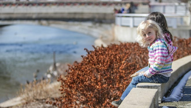 Juniper Stilley (front), and Emily Williams in March watch ducks along the Central Canal in Broad Ripple. An estimated $2.25 million will redesign the canal's north bank from College to Guilford avenues.