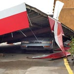 A car is crushed by a portion of the building at an Exxon gas station in Madison, Miss.