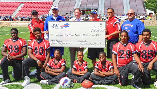 Franklin modified football team members with (back row, from left) Jason George, Franklin coach; Rex Ryan, Bills coach; Michael Clarke, executive director of Local Initiatives Support Corporation-Buffalo; Russ Brandon, Bills president; David Boundy, Franklin Campus athletic director; and Kevin Klein, Integrated Arts and Technology High School principal. A check for $200,000 was presented last year to help construct a new synthetic turf field.