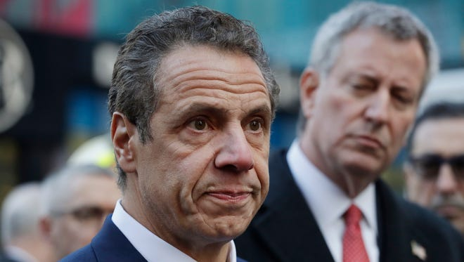 New York Gov. Andrew Cuomo, left, and Mayor Bill de Blasio attend a news conference, Monday, Dec. 11, 2017, outside the Port Authority Bus Terminal in New York. A pipe bomb strapped to a man went off in the subway near Times Square on Monday, injuring the suspect and another person at the height of the morning rush hour, law enforcement officials said.