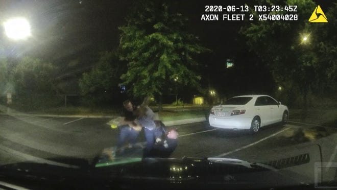 This screen grab taken from dashboard camera video provided by the Atlanta Police Department shows Rayshard Brooks, center, struggling with Officers Garrett Rolfe, left, and Devin Brosnan in the parking lot of a Wendy's restaurant, early Saturday, June 13, in Atlanta. Rolfe has been fired after the fatal shooting of Brooks and Brosnan has been placed on administrative duty. [Via AP)