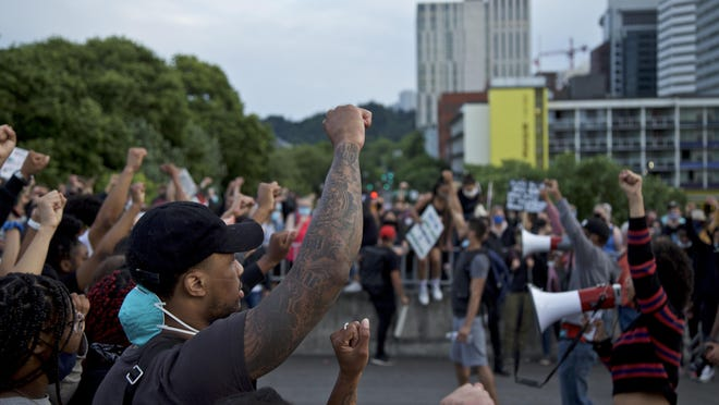 The Portland Trail Blazers' Damian Lillard, left, joins other demonstrators in Portland on Thursday during a protest against police brutality and racism, sparked by the death of George Floyd, who died May 25 after being restrained by police in Minneapolis.