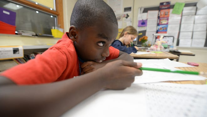 Lamonte Jackson concentrates on his homework along with classmate Alleah Luisier during the YMCA after school program at Eisenhower Elementary School.