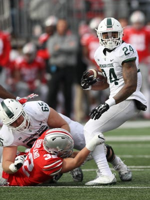 Michigan State's Gerald Holmes is tackled by Ohio State's Tuf Borland in the third quarter Nov. 11.