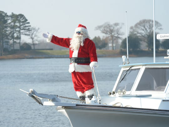 """Santa waves to onlookers as he approaches the Onancock Wharf Saturday, Dec. 13, 2014. Santa's arrival by boat was one of the featured activities during this year's """"Christmas in Onancock"""" sponsored by the town's business and civic association."""