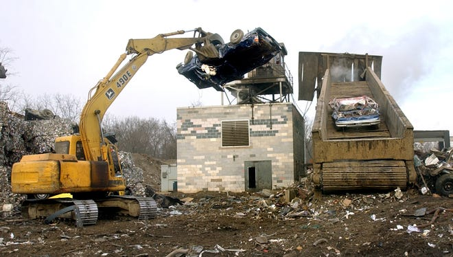 "Dennis Eaton lifts a crushed car on to the conveyor belt of the ""shredder"" which breaks cars and scrap metal into small pieces to be recycled in steel mills. The shredder is located at J&K Salvage on Kings Mill road."