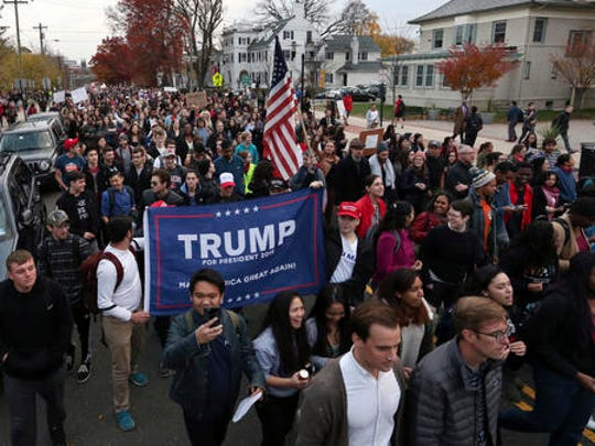 A few Donald Trump supporters carry a banner as they join hundreds of Rutgers University students blocking College Ave., in New Brunswick, N.J., as they march to protest some of President-elect Donald Trump's policies and to ask school officials to denounce some of his plans at Rutgers University Wednesday, Nov. 15, 2016, in New Brunswick, N.J. College students at campuses around the United States say they are planning rallies and walkouts to call on school administrators to protect students and employees against immigration proceedings under Donald Trump's presidency.
