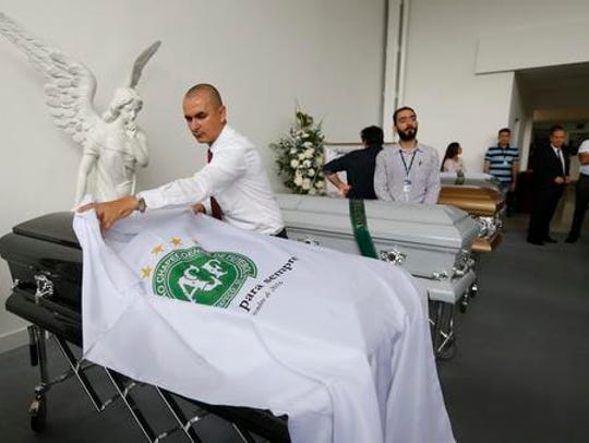 A funeral employee places a white sheet with a Chapecoense