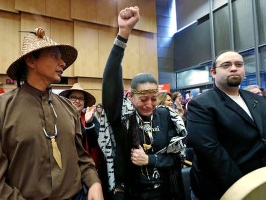 Olivia One Feather, center, of the Standing Rock Sioux tribe, holds her fist up and cries tears of happiness after the Seattle City Council voted to divest from Wells Fargo over its role as a lender to the Dakota Access pipeline project and other business practices, Tuesday, Feb. 7, 2017, in Seattle.  Wells Fargo manages more than $3 billion of Seattle's operating account.
