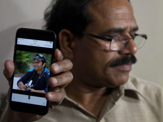 A man shows a picture of Alok Madasani, an engineer who was injured in the shooting Wednesday night in a crowded suburban Kansas City bar, on a mobile phone as Madasani's father Jaganmohan Reddy talks to the media at his residence in Hyderabad, India, Friday, Feb. 24, 2017. The shooting of two Indians in the crowded suburban Kansas City bar has sent shock waves through their hometowns, and India's government is rushing diplomats to monitor progress in investigation into the crime. The suspect, Adam Purinton, has been taken into custody and charged on Thursday with murder and attempted murder.