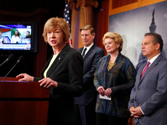 Sen. Tammy Baldwin, D-Wis., left, accompanied by, from second from left,  Rep. Don Beyer, D-Va., Sen. Debbie Stabenow, D-Mich., and Rep. David Cicilline, D-R.I., speaks during a news conference on Capitol Hill in Washington, Tuesday, April 25, 2017, to discuss President Donald Trump's first 100 days.