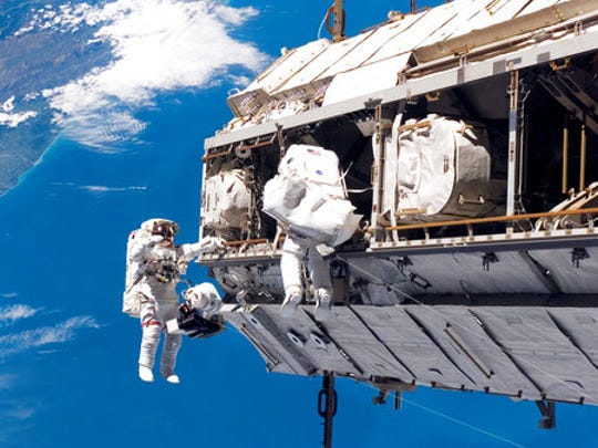 In this Dec. 12, 2006 photo made available by NASA, astronaut Robert L. Curbeam Jr., left, and European Space Agency astronaut Christer Fuglesang, participate in a spacewalk during construction of the International Space Station. In the background are New Zealand and the Pacific Ocean. According to a report released Wednesday, April 26, 2017, NASA is managing a variety of design and health risks associated with the spacewalking suits used by astronauts aboard the International Space Station. The suits were developed more than 40 years ago and intended for only 15 years' use.