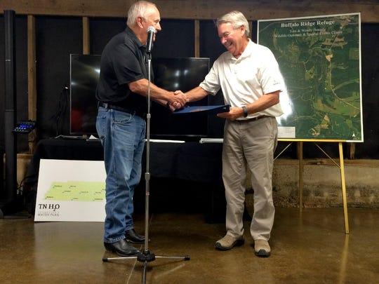 Deputy Gov. Jim Henry presents Tom Beasley with a state
