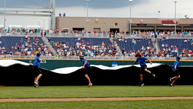 Grounds crew puts the tarp on the field before the game between the Arizona Wildcats and Coastal Carolina Chanticleers in game three of the College World Series championship series at TD Ameritrade Park.