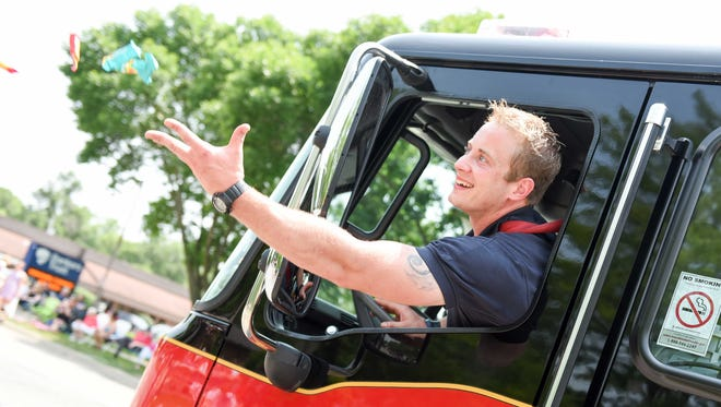 Windsor Heights firefighter Blake Wheeler throw candy to the kids on Saturday, July 4, 2015, during the Windsor Heights 4th of July parade.