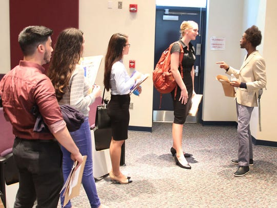 Designer Sabre Mochachino, right, speaks to students after the Speed Communication Workshop March 23 at Indian River State College's Pruitt Campus.