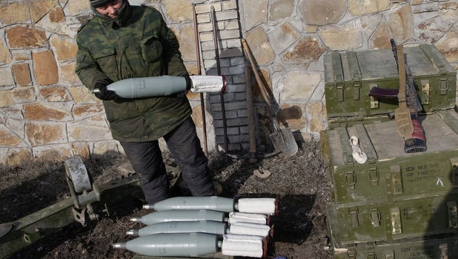 A pro-Russian separatist holds a shell as he takes position not far from the eastern Ukrainian city of Debaltseve, on Feb. 19, 2015.