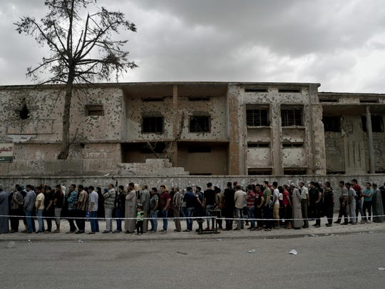 Iraqis wait in a long line to cast their vote in the