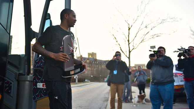 Gary Clark walks off the Bearcats team bus, holding the American Athletic Conference Championship trophy Sunday, March 34th at the University of Cincinnati