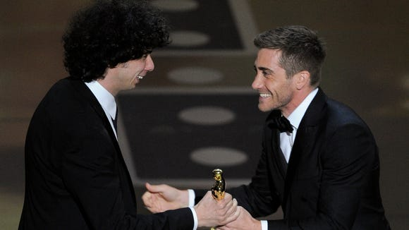 """Jake Gyllenhaal hands Luke Matheny his Oscar for best live action short film for """"God of Love"""" at the 83rd Academy Awards in 2011."""