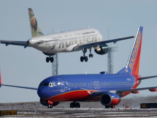 A Southwest Airlines plane waits to take off as a Frontier